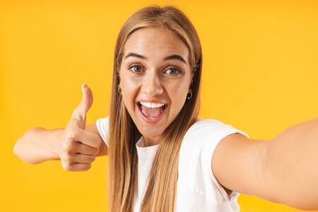 Image of cute woman in basic clothes smiling and showing thumb up while taking selfie photo isolated over yellow Reklamní fotografie