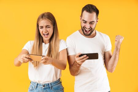 Image of excited couple man and woman in basic t-shirts playing video games on smartphones together isolated over yellow Reklamní fotografie