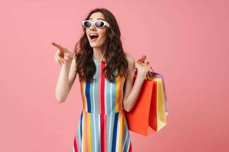 Image of beautiful shocked suprised positive young cute woman posing isolated over pink wall background holding shopping bags pointing aside.