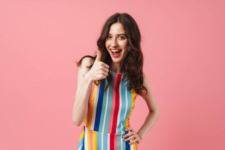 Photo of beautiful happy positive cute woman posing isolated over pink wall background showing thumbs up. Reklamní fotografie