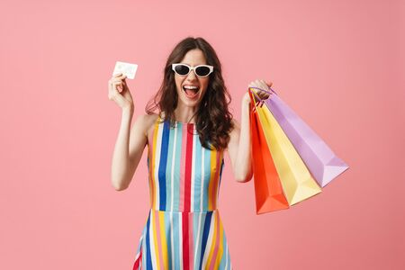 Photo of beautiful positive emotional young cute woman posing isolated over pink wall background holding shopping bags and credit card make winner gesture.