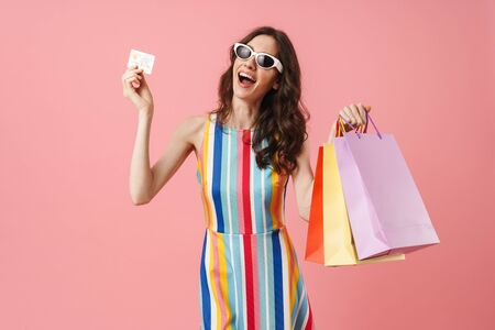 Photo of beautiful positive smiling cute woman posing isolated over pink wall background holding shopping bags and credit card make winner gesture. Фото со стока