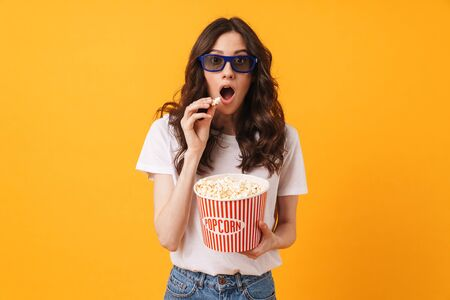 Photo of shocked young woman posing isolated over yellow wall background eat popcorn watch film.