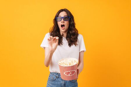 Photo of scared shocked young woman posing isolated over yellow wall background eat popcorn watch film. Фото со стока