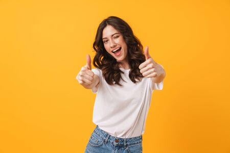 Image of beautiful brunette woman wearing casual clothes winking and showing thumbs up at camera isolated over yellow background