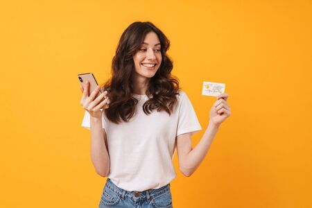 Photo of pleased young woman posing isolated over yellow wall background using mobile phone holding debit card. Фото со стока