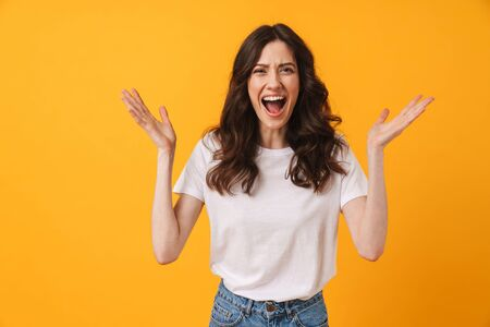 Photo of emotional screaming young woman posing isolated over yellow wall background.