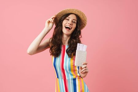 Picture of optimistic pleased positive happy young cute woman posing isolated over pink wall background holding passport with tickets.