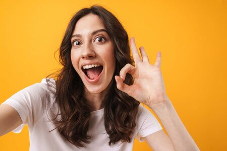 Photo of smiling cheerful young woman posing isolated over yellow wall background take a selfie by camera showing thumbs up gesture. Reklamní fotografie