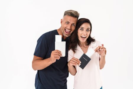 Cheerful attractive couple wearing casual outfit standing isolated over white background, showing passports with flight tickets