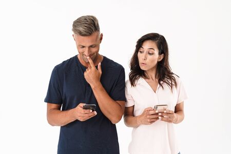 Attractive couple wearing casual outfit standing isolated over white background, using mobile phone, woman looking at mans phone Banco de Imagens
