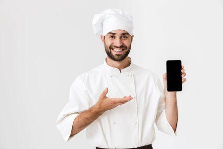 Afbeelding van een positief lachende jonge chef-kok die zich voordeed op een witte muurachtergrond in een uniforme mobiele telefoon met een leeg scherm.