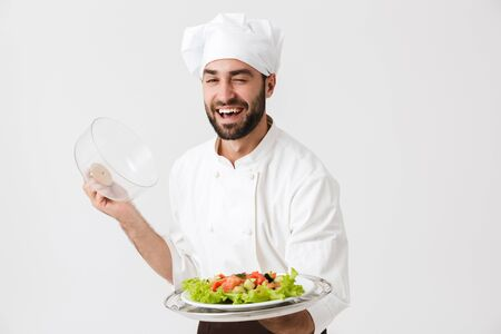 Image of handsome chief man in cook uniform smiling and holding plate with vegetable salad isolated over white wall Reklamní fotografie