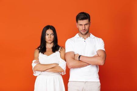 Attractive upset young couple standing with arms folded isolated over red background Imagens