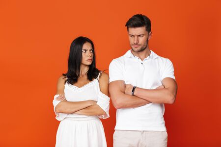 Attractive upset young couple standing with arms folded isolated over red background, looking at each other
