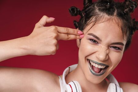 Image of crazy punk girl with bizarre hairstyle wearing headphones smiling while doing kill gesture with fingers isolated over red background Reklamní fotografie
