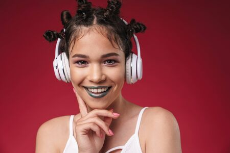 Image of beautiful punk girl with bizarre hairstyle and dark lipstick smiling while listening to music with headphones isolated over red background Reklamní fotografie
