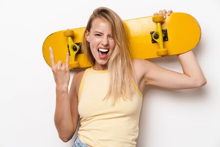 Image of impudent amazing young pretty woman posing isolated over white wall background holding skateboard showing rock gesture. Фото со стока