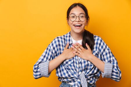 Photo of a happy pleased emotional cute teenage girl in glasses posing isolated over yellow wall background.