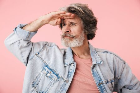 Portrait of a middle aged man wearing casual outfit standing isolated over pink background, looking far away