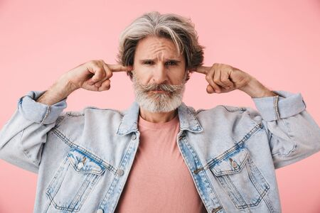 Portrait of an annoyed middle aged man wearing casual outfit standing isolated over pink background, covering ears Banco de Imagens