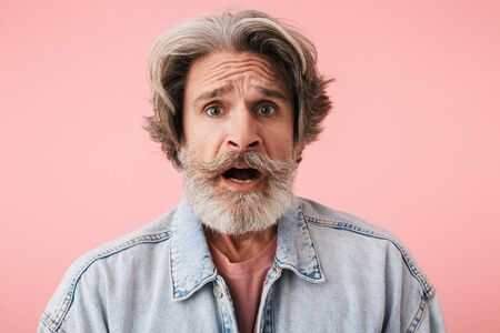 Portrait of a shocked middle aged man wearing casual outfit standing isolated over pink background