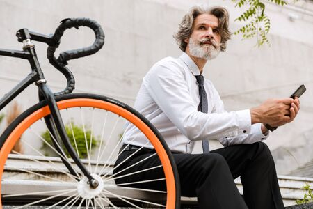 Handsome mature businessman in formalwear sitting on a bench with bicycle outdoors, texting a message