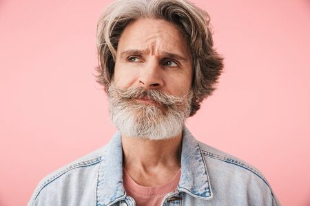 Portrait of brooding old man with gray beard thinking and looking at copyspace isolated over pink background
