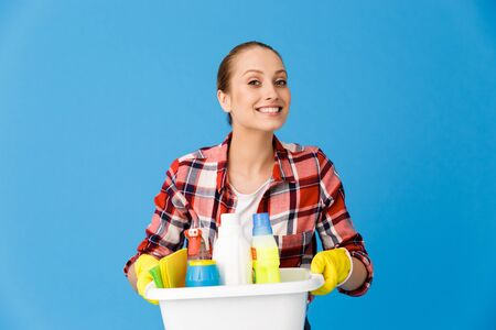 Portrait of smiling housewife in rubber gloves holding basin with detergent bottles and washing cleansers while doing housework isolated over blue background