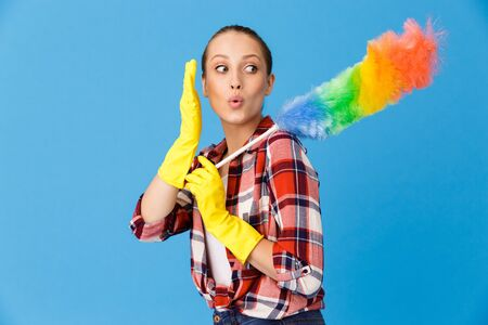 Portrait of beautiful housewife wearing yellow rubber gloves holding colorful duster while doing housework and cleaning room isolated over blue background Stock fotó
