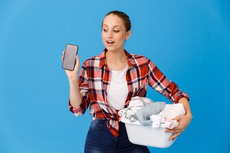 Portrait of beautiful housewife carrying basin with clean clothes and holding cellphone while doing housework isolated over blue background Stock fotó