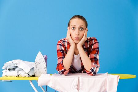 Portrait of surprised housewife wearing casual plaid shirt ironing clean clothes on board while doing housework isolated over blue background Stock fotó