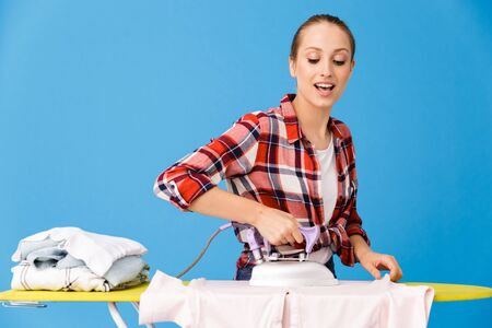 Portrait of content housewife wearing casual plaid shirt ironing clean clothes on board while doing housework isolated over blue background Stock fotó