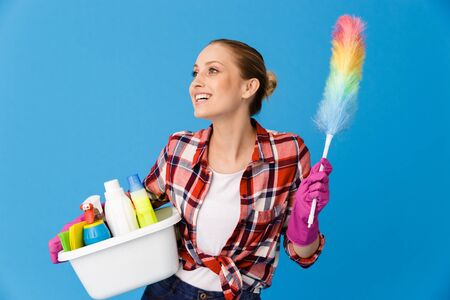 Portrait of beautiful housewife in rubber gloves holding basin with detergent bottles and colorful duster while doing housework isolated over blue background