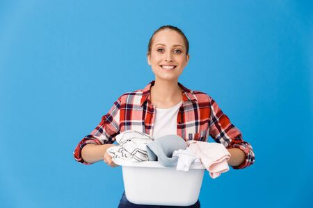 Portrait of young housewife smiling and carrying basin with clean clothes while doing housework isolated over blue background Stock fotó
