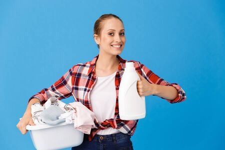 Portrait of young housewife carrying basin with clean clothes and holding laundry detergent isolated over blue background Stock fotó
