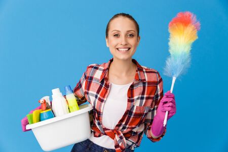 Portrait of happy housewife in rubber gloves holding basin with detergent bottles and colorful duster while doing housework isolated over blue background Stock fotó