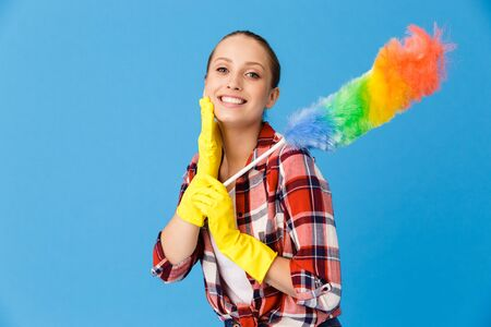 Portrait of optimistic housewife wearing yellow rubber gloves holding colorful duster while doing housework and cleaning room isolated over blue background