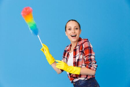 Portrait of cheerful housewife wearing yellow rubber gloves holding colorful duster while doing housework and cleaning room isolated over blue background