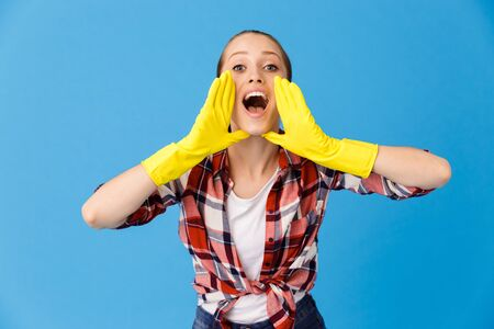 Portrait of lovely housewife wearing yellow rubber gloves screaming at camera while doing housework and cleaning room isolated over blue background