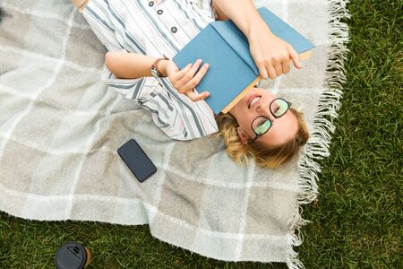 Top view of a beautiful young blonde girl relaxing on a lawn at the park, reading a book while laying on a blanket