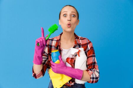 Portrait of happy housewife in rubber gloves holding detergent bottles and washing brush while doing housework isolated over blue background