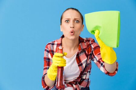 Portrait of uptight housewife in yellow rubber gloves holding detergent sprayer and cleaning rag while doing housework isolated over blue background
