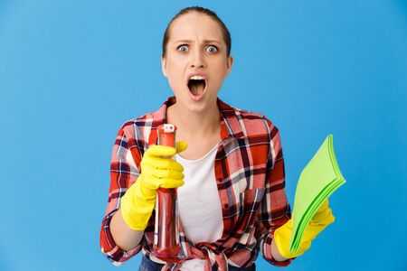 Portrait of excited housewife in yellow rubber gloves holding detergent sprayer and cleaning rag while doing housework isolated over blue background