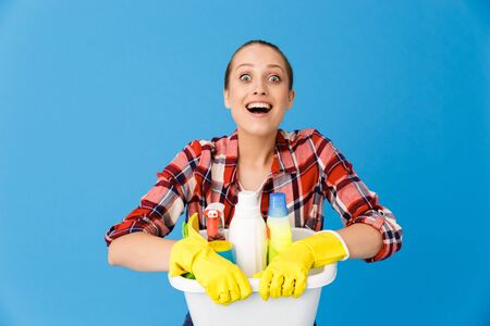 Portrait of joyful housewife in rubber gloves holding basin with detergent bottles and washing cleansers while doing housework isolated over blue background Stock fotó