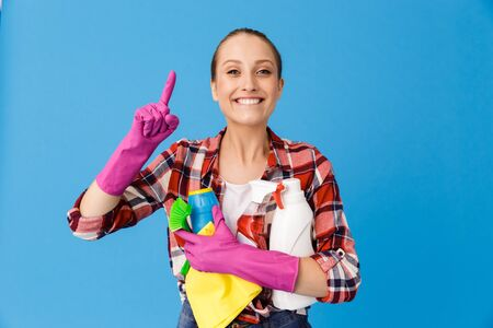 Portrait of cheerful housewife in rubber gloves holding detergent bottles and washing cleansers while doing housework isolated over blue background