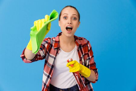 Portrait of brunette housewife in yellow rubber gloves holding detergent sprayer and cleaning rag while doing housework isolated over blue background