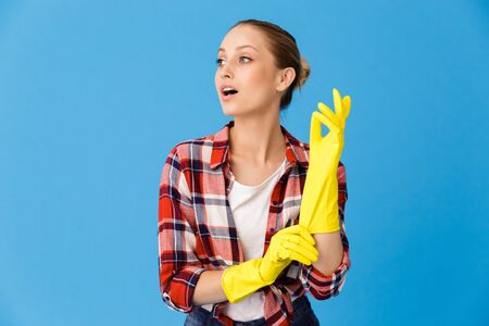 Portrait of lovely housewife wearing yellow rubber gloves while doing housework and cleaning room isolated over blue background