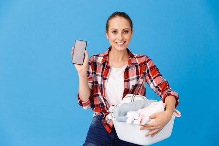 Portrait of attractive housewife carrying basin with clean clothes and holding cellphone while doing housework isolated over blue background