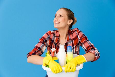 Portrait of content housewife in rubber gloves holding basin with detergent bottles and washing cleansers while doing housework isolated over blue background